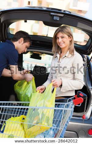 young couple arranging shopping bags in car - stock photo