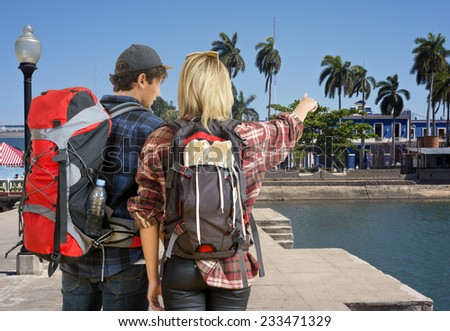 Young couple, arriving at a tropical resort, looking for a place or hostel to stay - stock photo