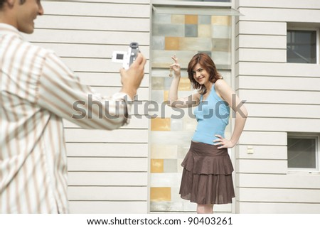Young couple arriving at their new home, holding the house key and recording the moment.