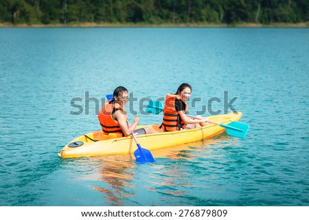 Young couple Asia paddling in kayak on lake - stock photo