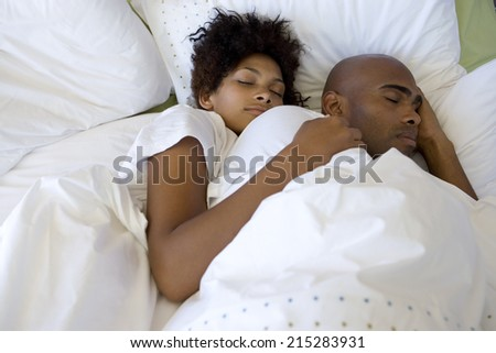 Young couple asleep in bed, elevated view - stock photo