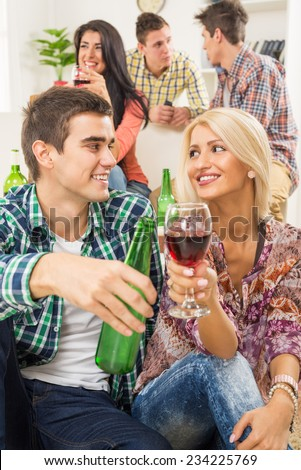 Young couple at a home party, sit on the floor and knocking with drinks, in the background you can see their friends who are sitting on the couch. - stock photo
