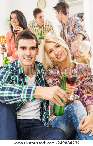 Young couple at a house party, sit on the floor and knocking with drinks, with a smile looking at the camera. In the background you can see their friends who are sitting on the couch. - stock photo
