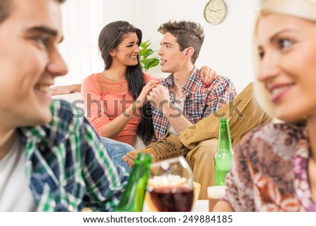 Young couple at a house party, sit on the floor, behind them is another young couple which is in the foreground, sitting on the couch and look at each other. - stock photo
