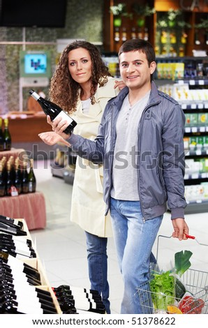 Young couple at a shelf with alcohol in shop - stock photo