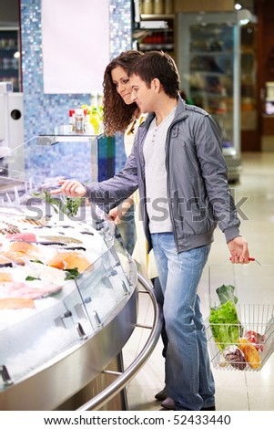 Young couple at a shelf with seafood in shop - stock photo