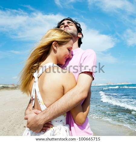 Young couple at beach, embracing, side view. Natural emotions. Happy life - stock photo