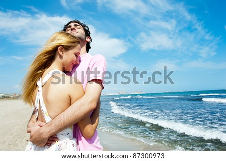 Young couple at beach, embracing, side view. Natural emotions. Happy life