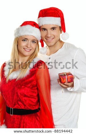 young couple at christmas with santa claus caps - stock photo