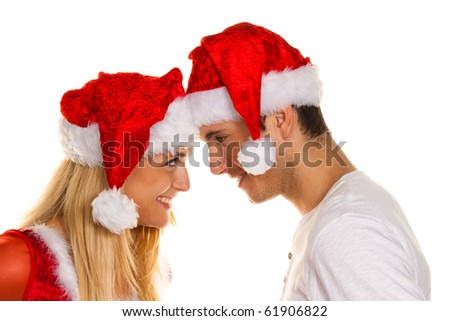 Young couple at Christmas with Santa Claus hats - stock photo