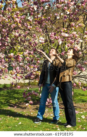 young couple?at?flowering tree - stock photo