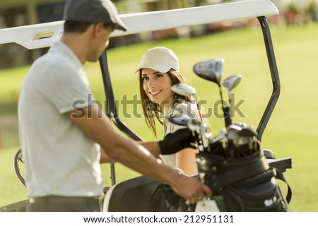Young couple at golf cart - stock photo