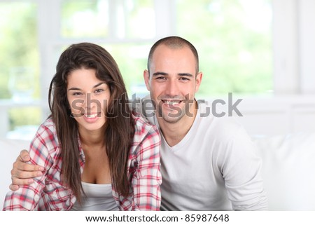 Young couple at home sitting in couch - stock photo