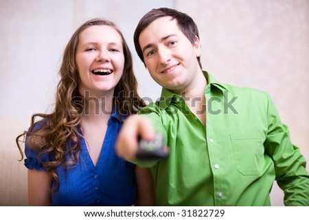 Young couple at home watching TV - stock photo