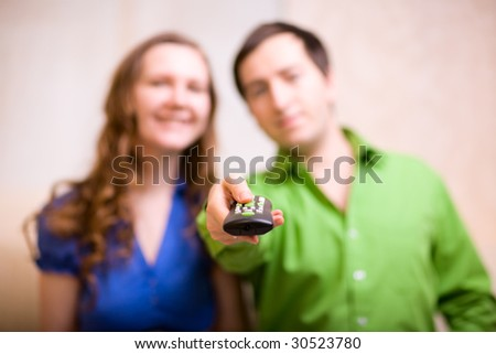 Young couple at home watching TV. Focus on remote control. - stock photo