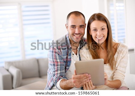 Young couple at home websurfing on internet - stock photo
