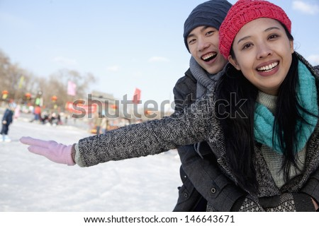 Young couple at ice rink - stock photo