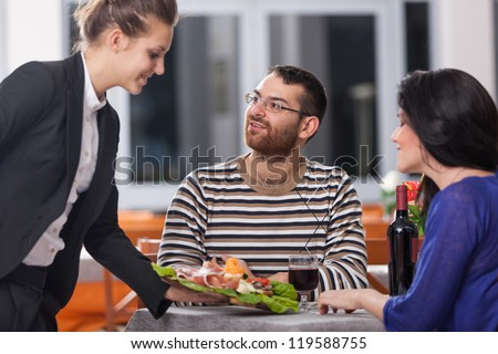 Young Couple at Restaurant with Waitress - stock photo