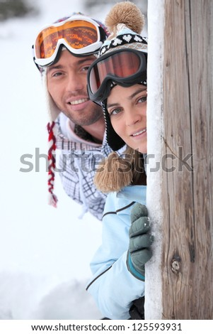 young couple at ski resort hiding behind wooden post - stock photo