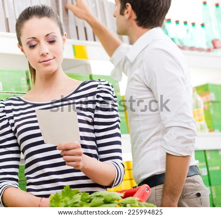 Young couple at supermarket checking shopping list and choosing products. - stock photo