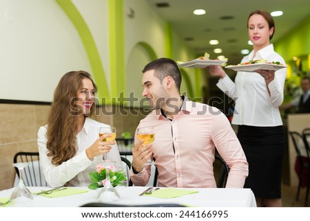 Young couple at table and waitress with plates in restaurant - stock photo