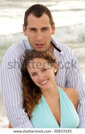 young couple at the beach in the gulf of mexico having a discussion with waves crashing behind them. - stock photo