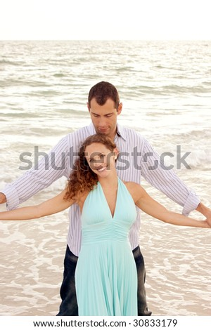 young couple at the beach in the gulf of mexico with man standing behind the woman facing the viewer with arms outstretched with waves crashing behind them. Woman is smiling and looking at viewer. - stock photo