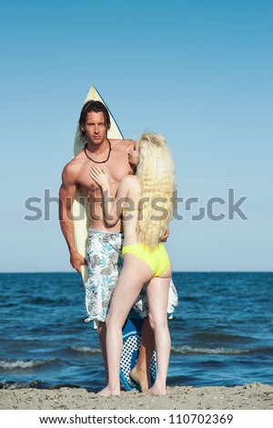 Young couple at the beach with surfboard. - stock photo