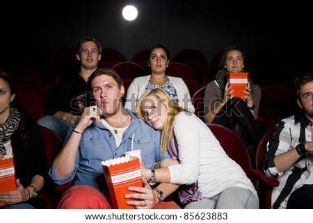 Young Couple at the Movie Theater eating popcorn - stock photo