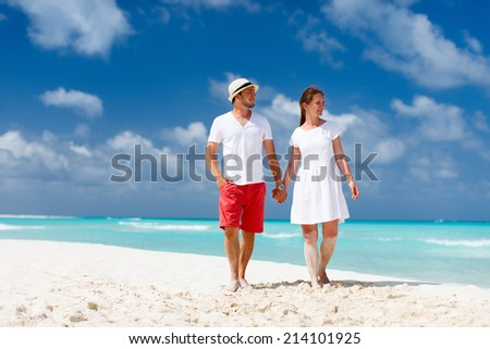 Young couple at tropical beach during summer vacation - stock photo