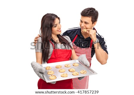 Young couple baking and eating cookies together isolated on white background