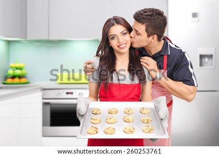 Young couple baking cookies in the kitchen at home  - stock photo
