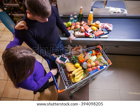 Young couple before checkout in supermarket - stock photo