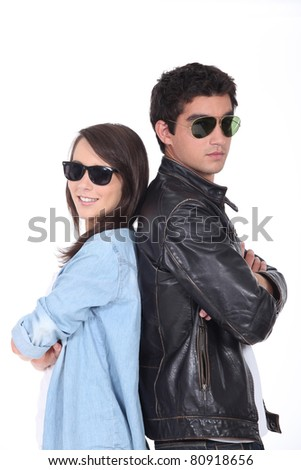 Young couple being cool in sunglasses and leather jacket - stock photo
