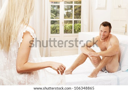 Young couple being playful in the bedroom. - stock photo