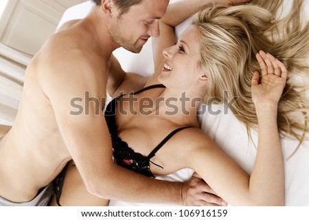 Young couple being playful in the bedroom.