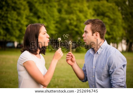 Young couple blowing out dandelions to each others face - stock photo