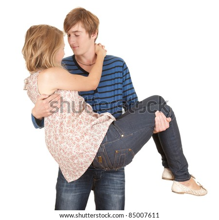 young couple, boyfriend carrying girl in his arms, white background - stock photo