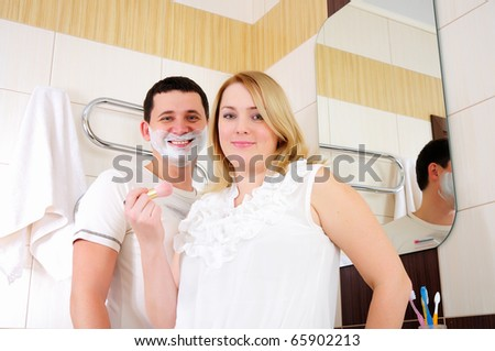 Young couple brings himself up early in the morning in the bathroom. - stock photo