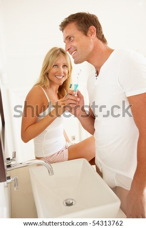 Young Couple Brushing Teeth In Bathroom