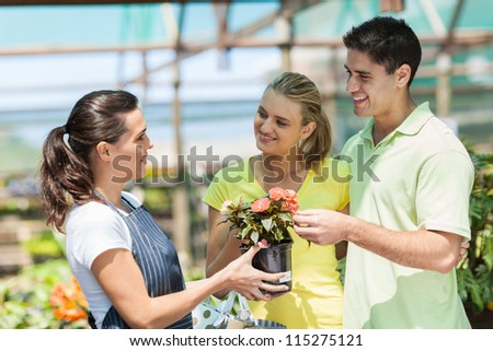 young couple buying flowers in nursery