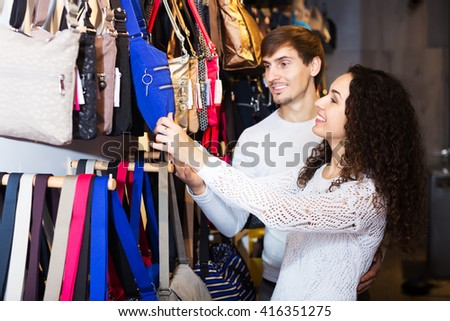 Young couple buying leather bags in haberdashery shop - stock photo