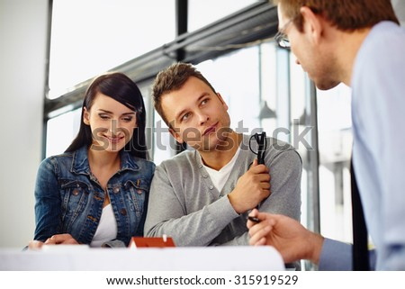 Young couple buying new home, talking with salesman - stock photo