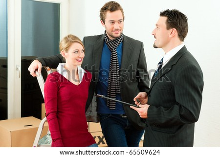 Young couple buying or renting a home or apartment, they are meeting the owner or real estate broker negotiating details - stock photo