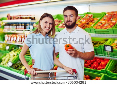 Young couple buying products in supermarket - stock photo