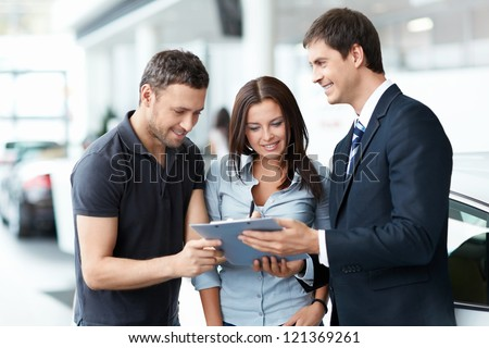 Young couple buys a car - stock photo