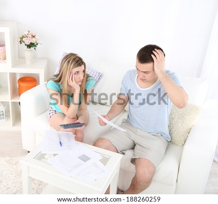 Young couple calculating finance at desk, on home interior background - stock photo