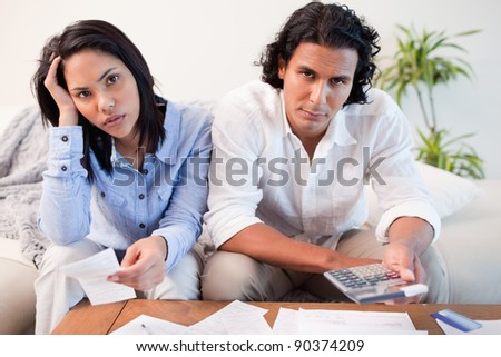 Young couple calculating their costs - stock photo
