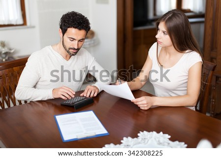 Young couple calculating their expenses - stock photo