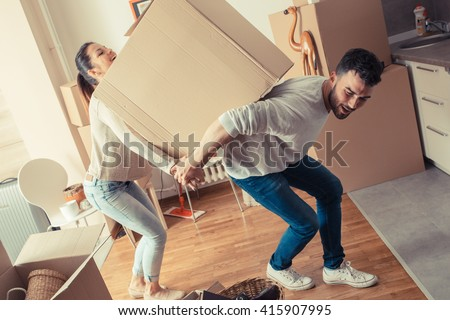 Young couple carrying big cardboard box at new home.Moving house. - stock photo